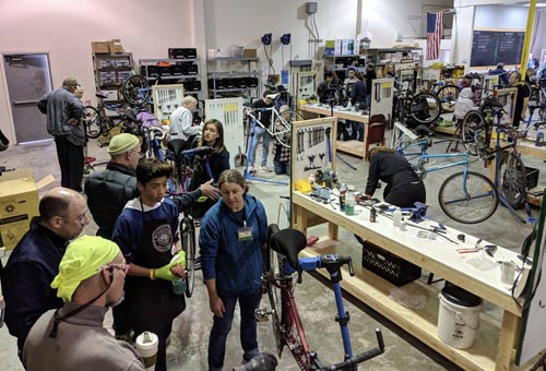 volunteers repairing bicycles in a large indoor workshop