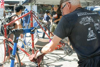 Man cleaning bicycle admidst other mechanics and bicycles at workday