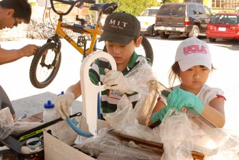 Father and two children repairing a bicycle