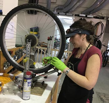 woman truing a bicycle wheel